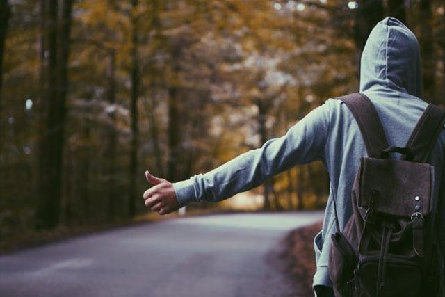 ヒッチハイクするフードの男性