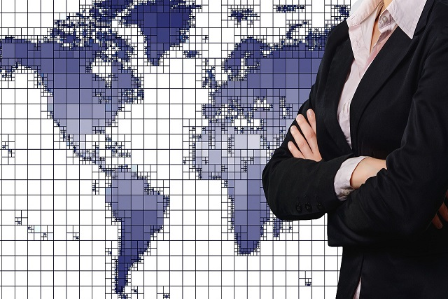 地図と腕を組んだ女性