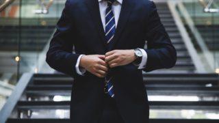 階段前に立つスーツ姿の男性