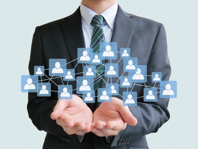 会社員の両手の上にネットワークのアイコンが繋がっている
