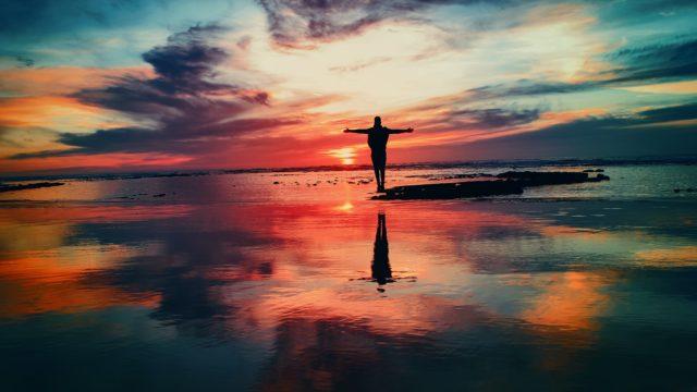 浅瀬で夕日をバックに両手を広げる人