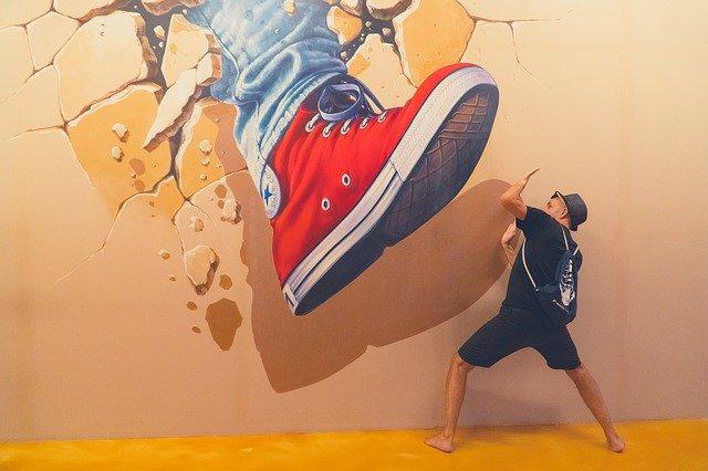 巨大な足のトリックアートの前でポーズをする男性