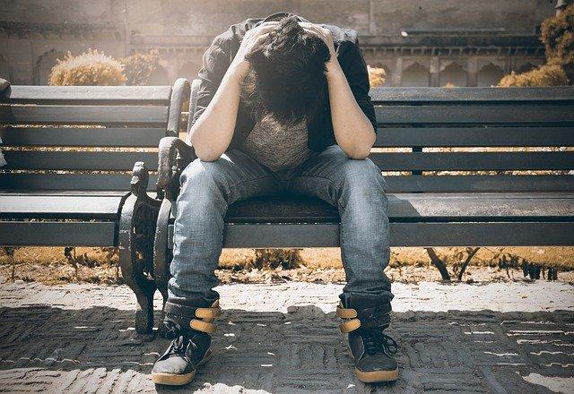ベンチに腰を下ろし頭を抱える男性