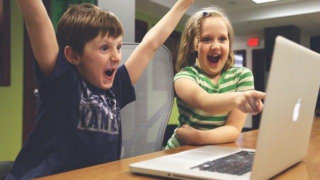 パソコンの前で喜ぶ子供たち