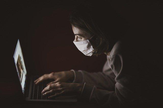 暗い中、パソコンを操作するマスクの男性