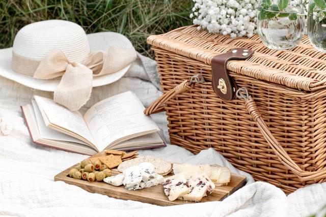 ピクニックで本、帽子、バスケットを広げる