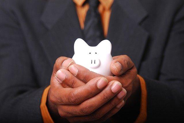 豚の貯金箱を両手で包んだビジネスマン