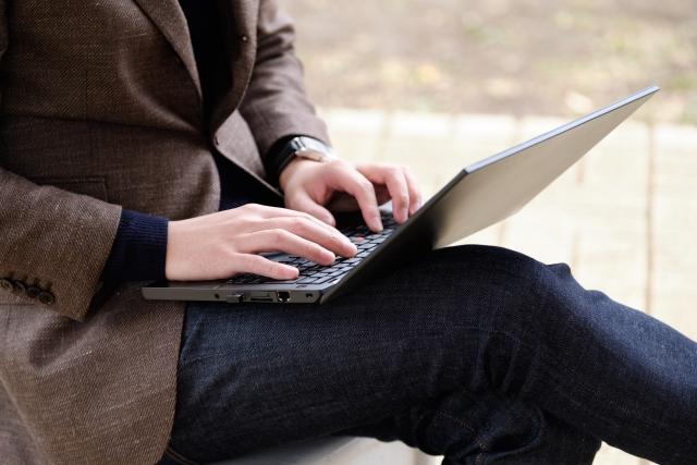 ベンチでパソコンを操作する男性