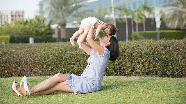 外で子供を抱き上げる母親