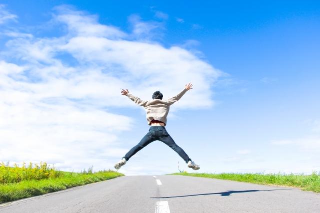 田舎道で両手を挙げてジャンプ