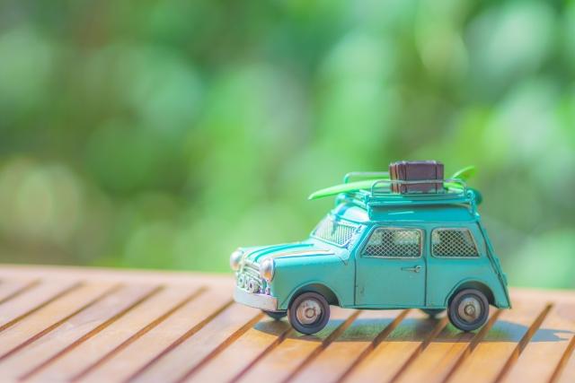 緑の背景に、車のミニチュア