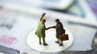 万札の上で握手するサラリーマンのフィギュア
