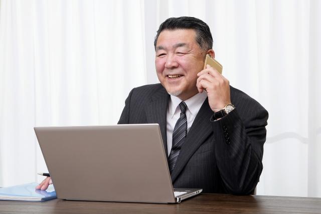 携帯で談笑するビジネスマン