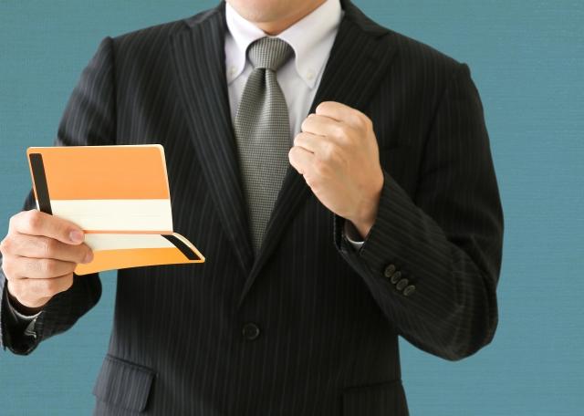 通帳を見てガッツポーズをするビジネスマン