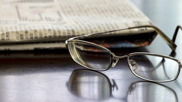 机の上の新聞紙と眼鏡