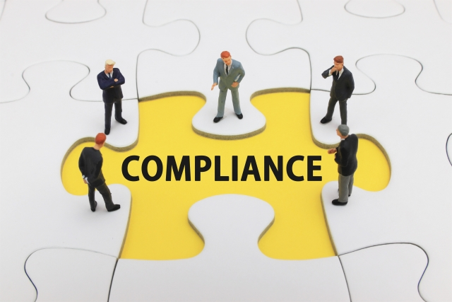 complianceのピースを囲んで話すビジネスマン