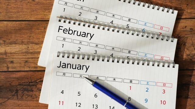 木製テーブルの上に並べたカレンダーとペン