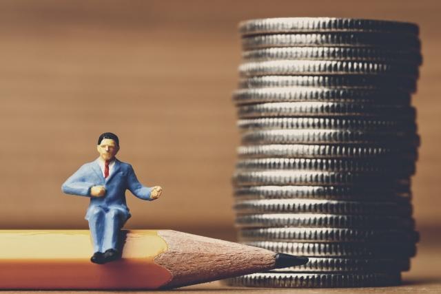 小銭と鉛筆の上に腰かけたビジネスマン