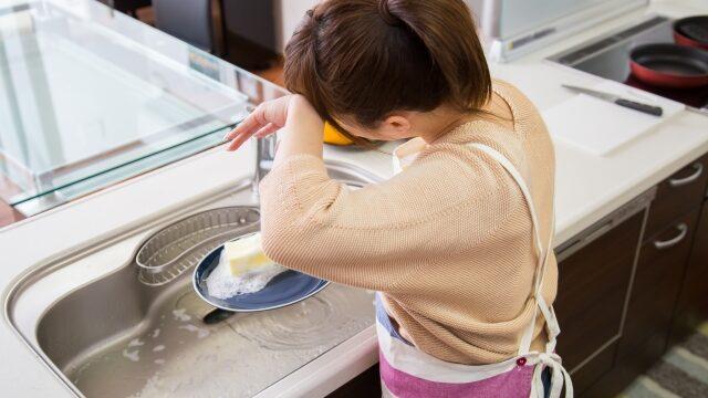 シンク掃除中に汗を拭く女性