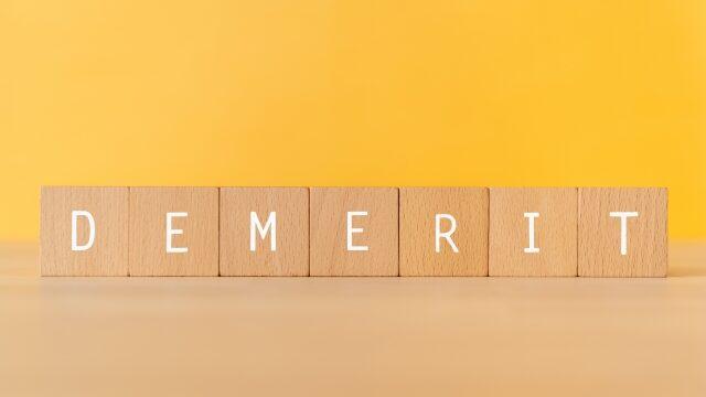 「DEMERIT」と書かれた積み木